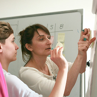 People discussing at the whiteboard
