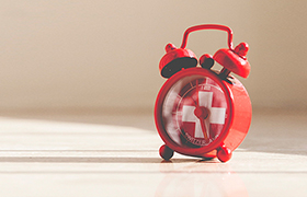 Red alarm clock with white cross